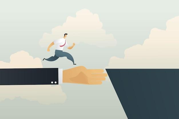Ręka biznesmena jest mostem, który pomaga biznesmenowi przebiec przez klif, aby osiągnąć swój cel