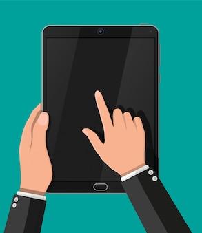 Ręką dotykając ekranu komputera typu tablet czarny.