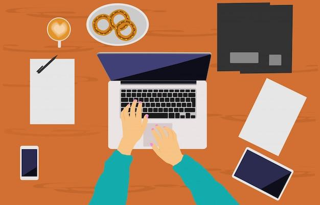 Ręka kobiety pracuje na notebooku umieszczonym na brązowym drewnianym biurku.