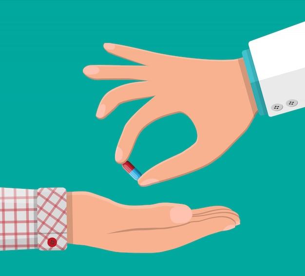 Ręka lekarza daje pacjentowi kapsułkę.