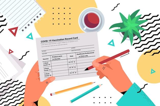Ręka lekarza podpisuje kartę szczepień przeciwko covid-19 globalny paszport odpornościowy certyfikat pcr wolny od ryzyka ponownej infekcji