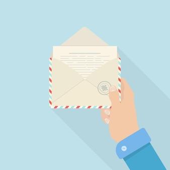 Ręka mężczyzny trzyma otwartą kopertę z listem. koncepcja korespondencji. e-maile i wiadomości przychodzące
