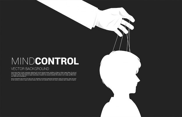 Ręka puppet master kontrolujący głowę sylwetka biznesmena. pojęcie manipulacji i mikrozarządzania