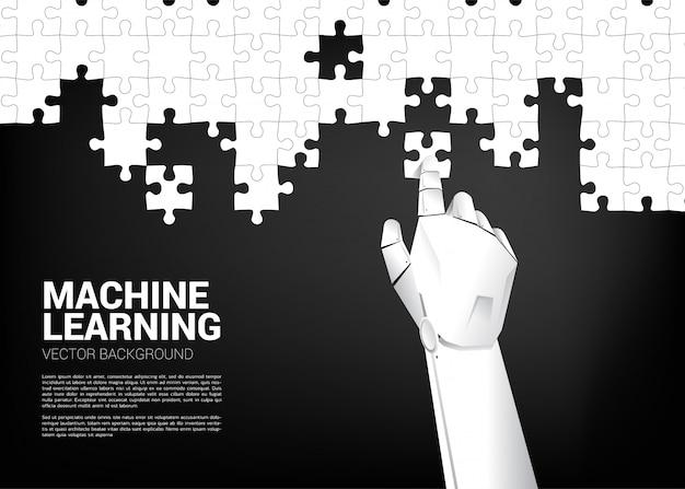 Ręka robota układa układankę.