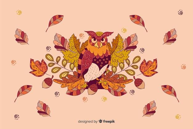 Ręka rysujący jesieni tło z sową