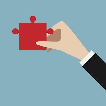 Ręka trzyma czerwony kawałek układanki. rozwiązanie, sukces, koncepcja biznesowa. ilustracja wektorowa eps 10, bez przezroczystości