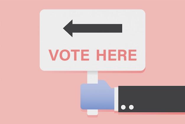 Ręka trzyma głosowanie tutaj znak.