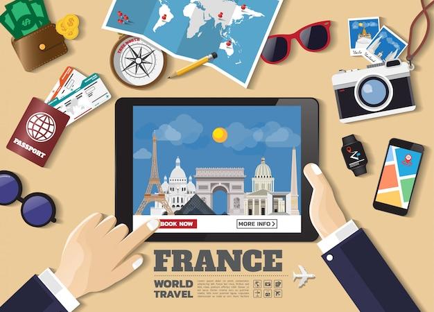 Ręka trzyma inteligentne urządzenie rezerwacji podróży przeznaczenia. znane miejsca we francji.