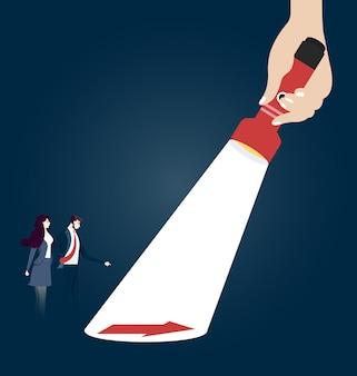 Ręka trzyma latarkę odkrywając ukryty znak strzałki. pomysł na biznes