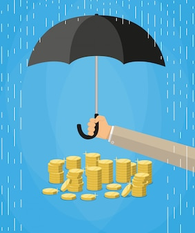 Ręka trzyma parasol do ochrony pieniędzy