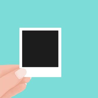 Ręka trzyma puste zdjęcie polaroid