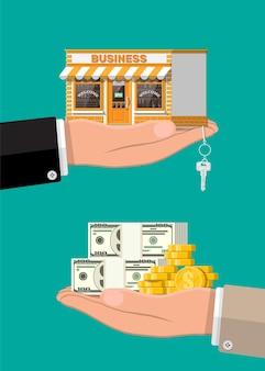 Ręka trzyma sklep lub nieruchomość komercyjną z kluczem i pieniędzmi