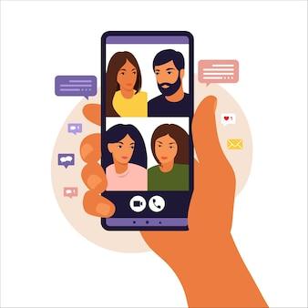 Ręka trzyma smartfon na czacie z przyjaciółmi podczas połączenia wideo. wideokonferencja z kolegami, dyskusja na odległość. płaski styl.