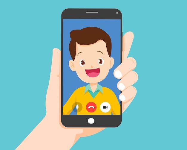 Ręka trzyma smartfon z inteligentnym człowiekiem na ekranie. rozmowa wideo z młodym mężczyzną