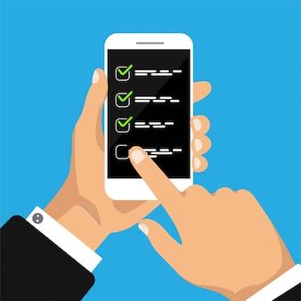 Ręka trzyma smartfona z listy zadań lub listy kontrolnej na ekranie smartfona.