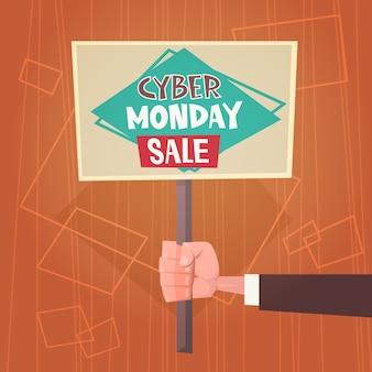 Ręka trzyma sztandar z tekstem cyber poniedziałek wyprzedaż oferty sprzedaży online