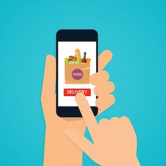 Ręka trzyma telefon inteligentny z dostawy żywności aplikacji. jedzenie w paczce. koncepcja e-commerce: zamów jedzenie online.