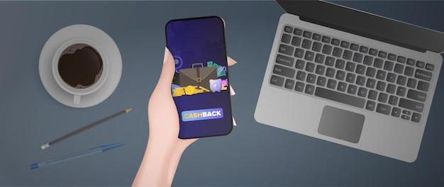 Ręka trzyma telefon z aplikacją płatniczą. przycisk płatności. karta kredytowa, złote monety, dolary, laptop, klawiatura, filiżanka kawy, długopis i ołówek. koncepcja sklepów internetowych, płatności i cashbacku. wektor