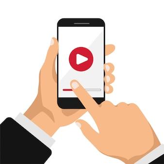 Ręka trzyma telefon z szablonem odtwarzacza wideo lub filmu na ekranie. koncepcja filmu.
