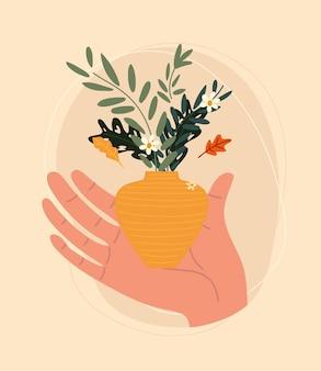Ręka trzyma wazon z kwiatami