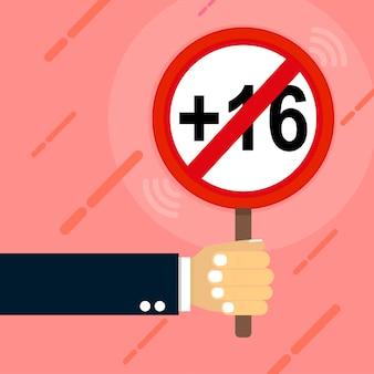 Ręka trzyma znak, który zaprzecza wieku 16 lat.