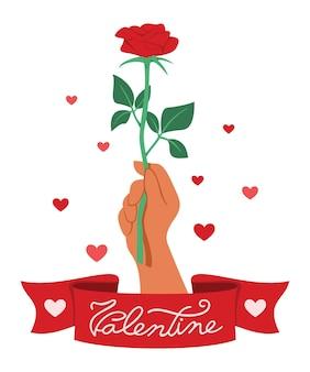 Ręka trzymająca czerwoną różę ze wstążką słowa to walentynki.