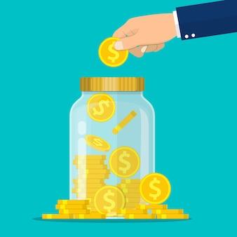 Ręka wrzuca złotą monetę do słoika. gotówka. zaoszczędź koncepcję pieniędzy.