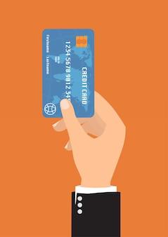 Ręka z błękitną kredytową kartą dla zapłaty.