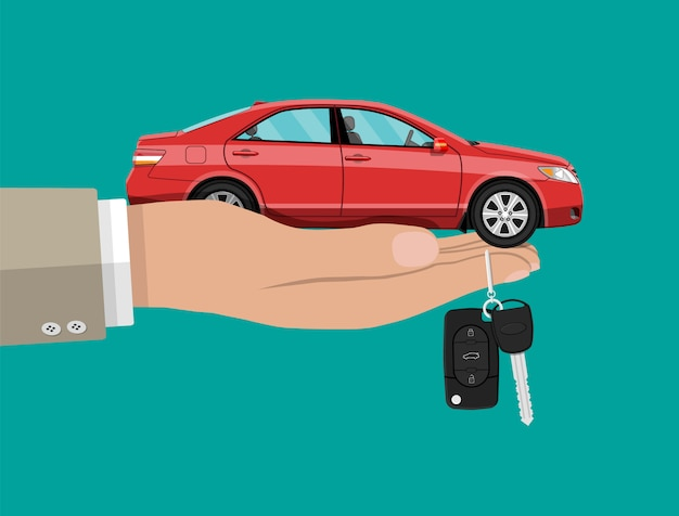 Ręka z czerwonym samochodem i kluczami