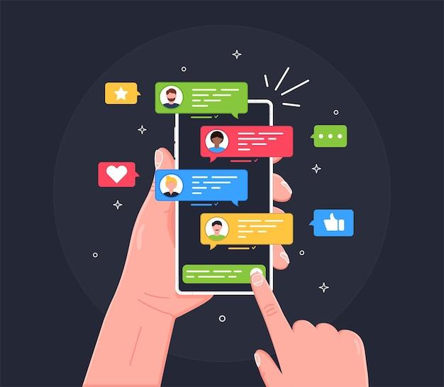 Ręka z telefonem i rozmawianie w komunikatorze ze znajomymi