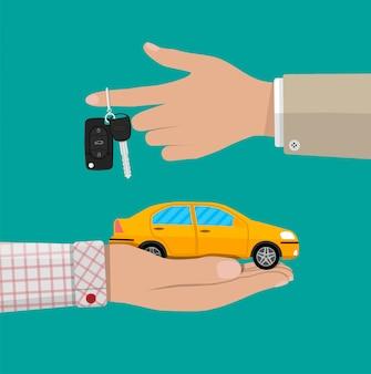 Ręka z żółtym samochodem i kluczami