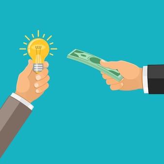 Ręka zmienia pieniądze na żarówkę