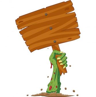 Ręka zombie kreskówka z ziemi trzymając pusty znak