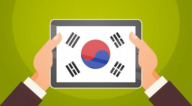 Ręki trzyma cyfrowej pastylkę z południowym korea