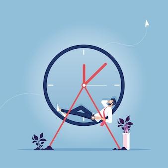 Relaks czas biznesmen trzymając się za ręce za głową i relaksując się na zegarze