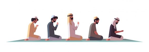 Religijnych muzułmańskich mężczyzn klęczących i modlących się na dywanie ramadan kareem święty miesiąc religia koncepcja mieszkanie na białym tle pełnej długości poziomej