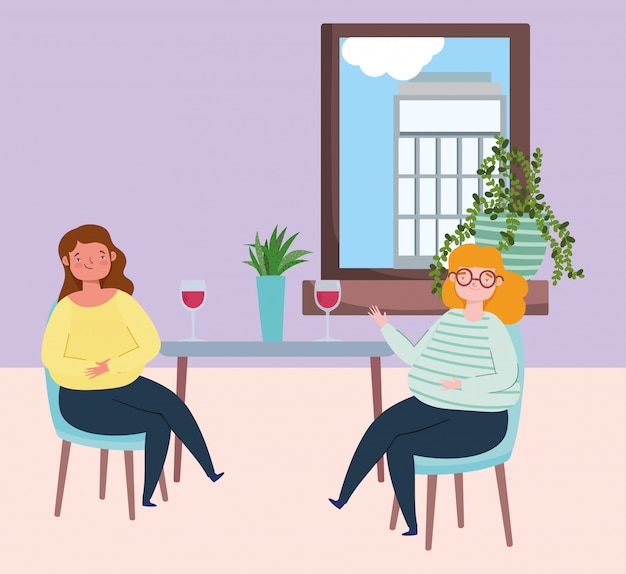 Restauracja lub kawiarnia zapewniająca dystans społeczny, młode kobiety przy kieliszku wina zachowują dystans