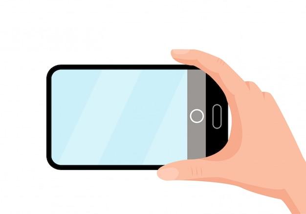 Robienie zdjęć na telefon. białe tło. ręka trzyma telefon.