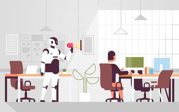 Robot trzyma megafon rozmawia z biznesmenem pracownik siedzi w miejscu pracy termin zarządzania termin sztucznej inteligencji technologia nowoczesne wnętrze biura