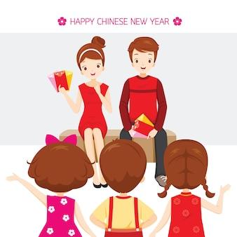Rodzic wręczający dzieciom czerwone koperty, tradycyjne świętowanie, chiny, szczęśliwego chińskiego nowego roku
