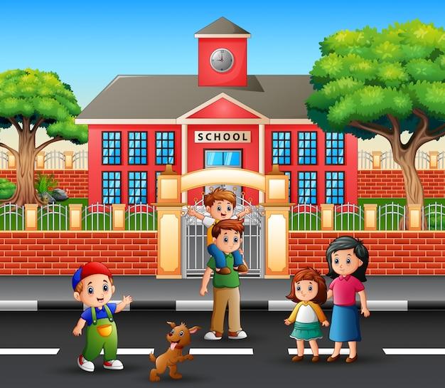 Rodzice i dzieci przed budynkiem szkoły