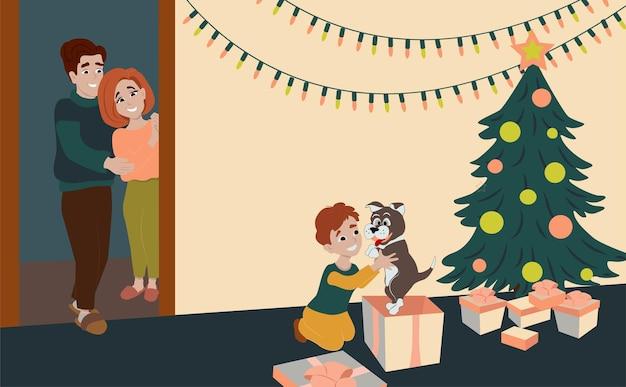 Rodzina daje synowi psa na boże narodzenie. szczęśliwe dziecko rozpakowuje prezenty pod choinką.