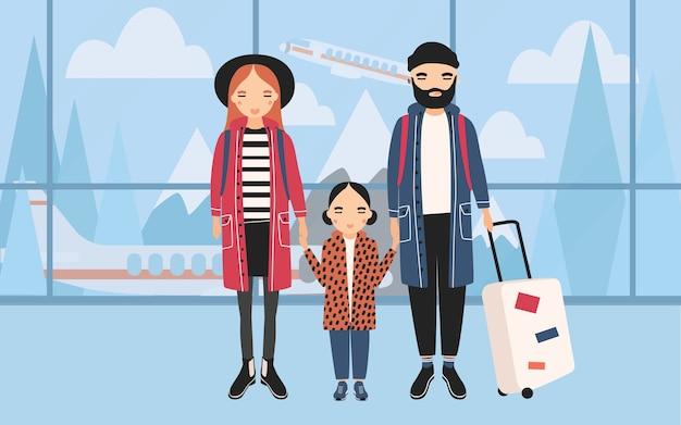 Rodzina na lotnisku. modna młoda para z dzieckiem i bagażem.