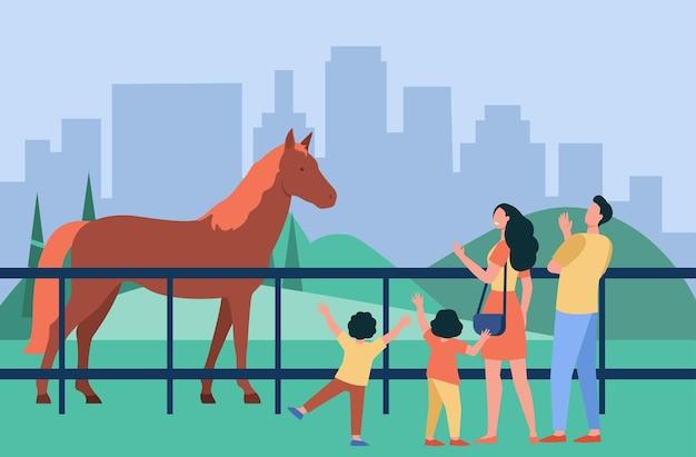 Rodzina patrząc na konia w parku miejskim. rodzice i dzieci odwiedzające zoo lub hipodrom