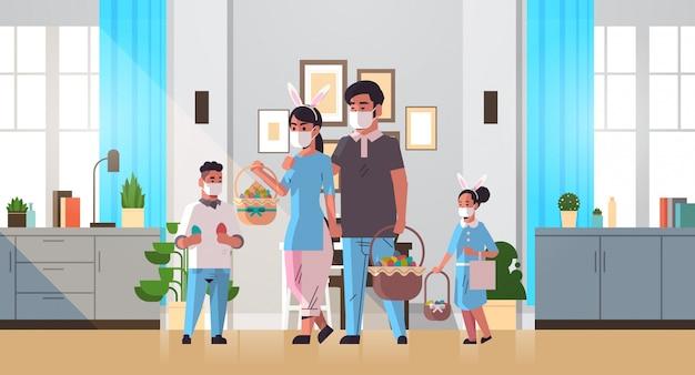 Rodzina trzyma kosze z jajami świętując szczęśliwe święta wielkanocne nosząc maskę, aby zapobiec koronawirusowi