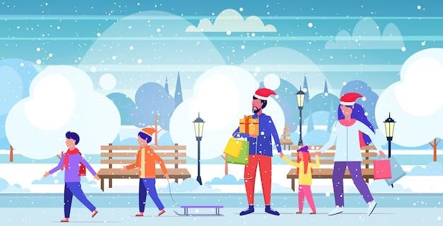 Rodzina w czapkach mikołaja spacery na świeżym powietrzu rodzice trzymający torby na zakupy dzieci bawiące się świąteczne zakupy koncepcja ferii zimowych miejski śnieżny park krajobraz