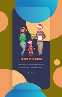 Rodzina w czapkach mikołaja trzyma pudełka z prezentami rodzice i córka świętują wesołych świąt szczęśliwego nowego roku ferie zimowe koncepcja ekran smartfona aplikacja mobilna online w pionie