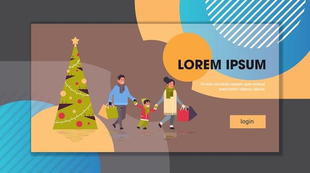 Rodzinny spacer z kolorowymi papierowymi torbami wesołych świąt szczęśliwego nowego roku zima zakupy koncepcja rodzice z dzieckiem trzyma sztandar zakupów