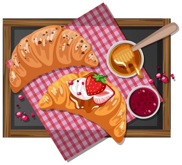 Rogalik śniadaniowy z dżemem truskawkowym na drewnianym talerzu na białym tle