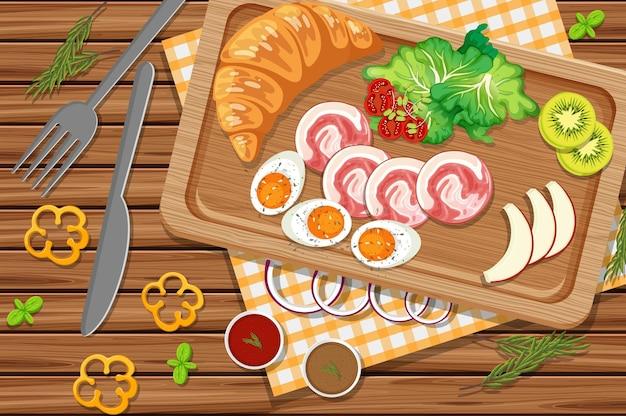 Rogalik śniadaniowy z szynką i gotowanym jajkiem na stole